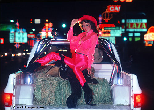 Photo of cowgirl in hot pink going down Las Vegas strip in back of a truck