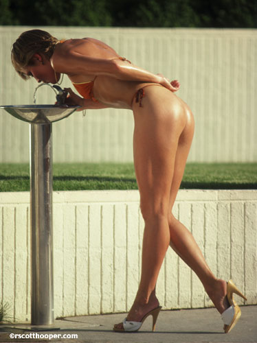 Photo of woman in thong drinking at fountain