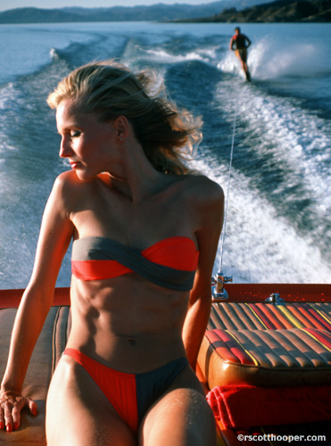 Photo of woman in bikini on boat with water skier