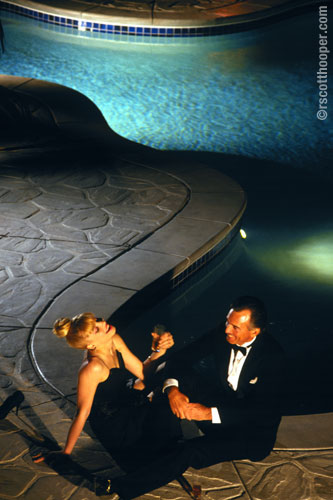 Photo of couple in evening dress by pool at night