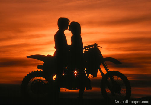 Photo of couple with motorcycle in silhouette at sunset