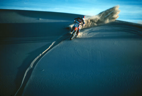 Photo of motorcycle racing on sand dune