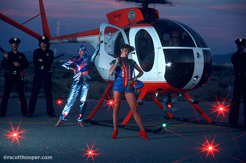 Photo of helicopter on the ground with two fashion models