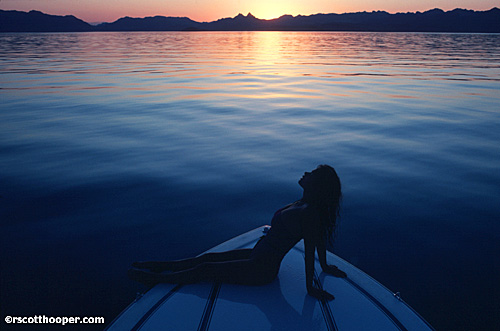 Image of girl in swimsuit on front of boat at sunset